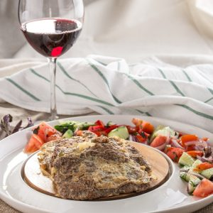 Homemade lamb schnitzel with fresh vegetable salad on the side and glass of red wine on tablecloth side view