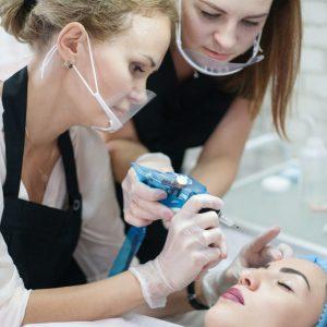 Decorative cosmetology practical training. Female intern using tattoo machine for eyebrow microblading.